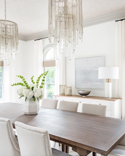 Glass chandelier hanging over dark wood table