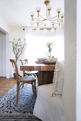 Gold and white chandelier hanging over natural wood table