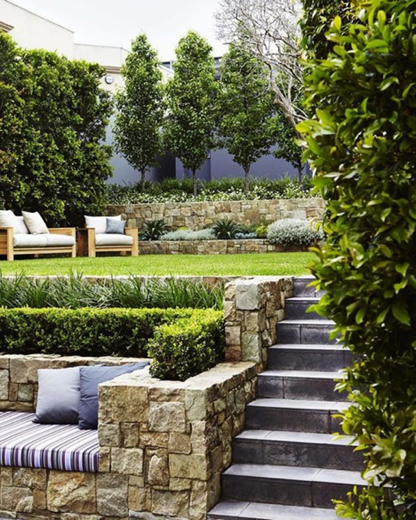 Small Grassy outdoor patio with stone steps and outdoor seating